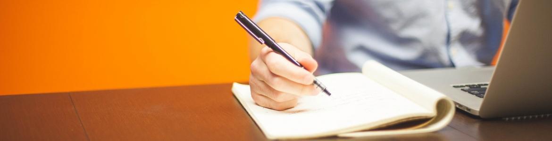 Imagen de mano de persona con bolígrafo escribiendo sobre una mesa