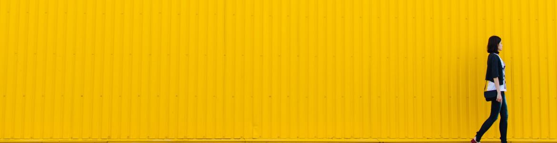 Chica caminando con pared amarilla de fondo