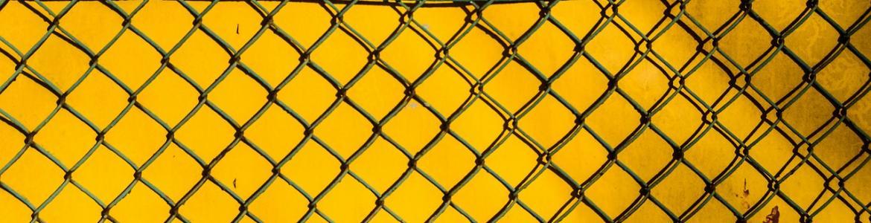 Detalle de una verja cruzada con un fondo amarillo