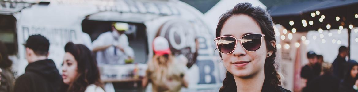 Primer plano de una chica sonriendo con trenzas y gafas de sol