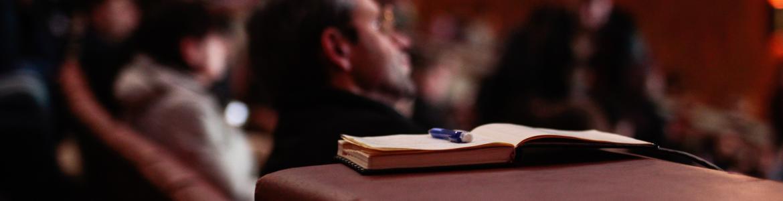 Una libreta sobre la silueta de una persona en un congreso