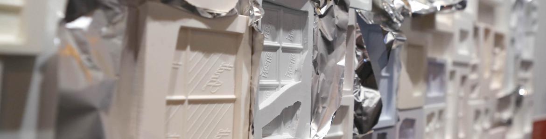 Placas de moldes de chocolates en distintos materiales plásticos y pegadas unas a otras como un panel en la parez