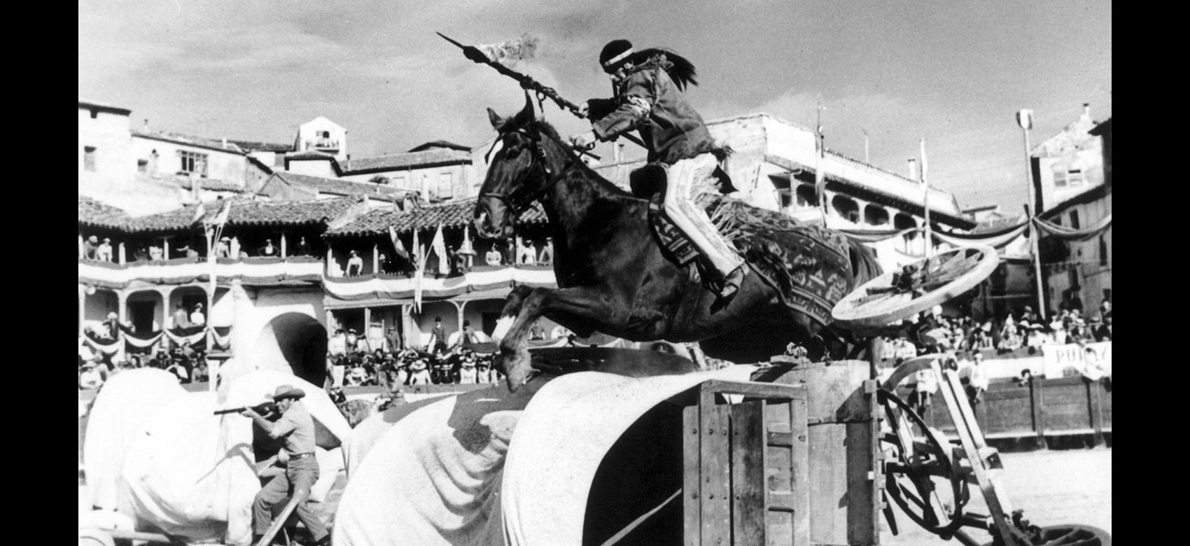 Fotograma de un indio saltando a caballo en una plaza