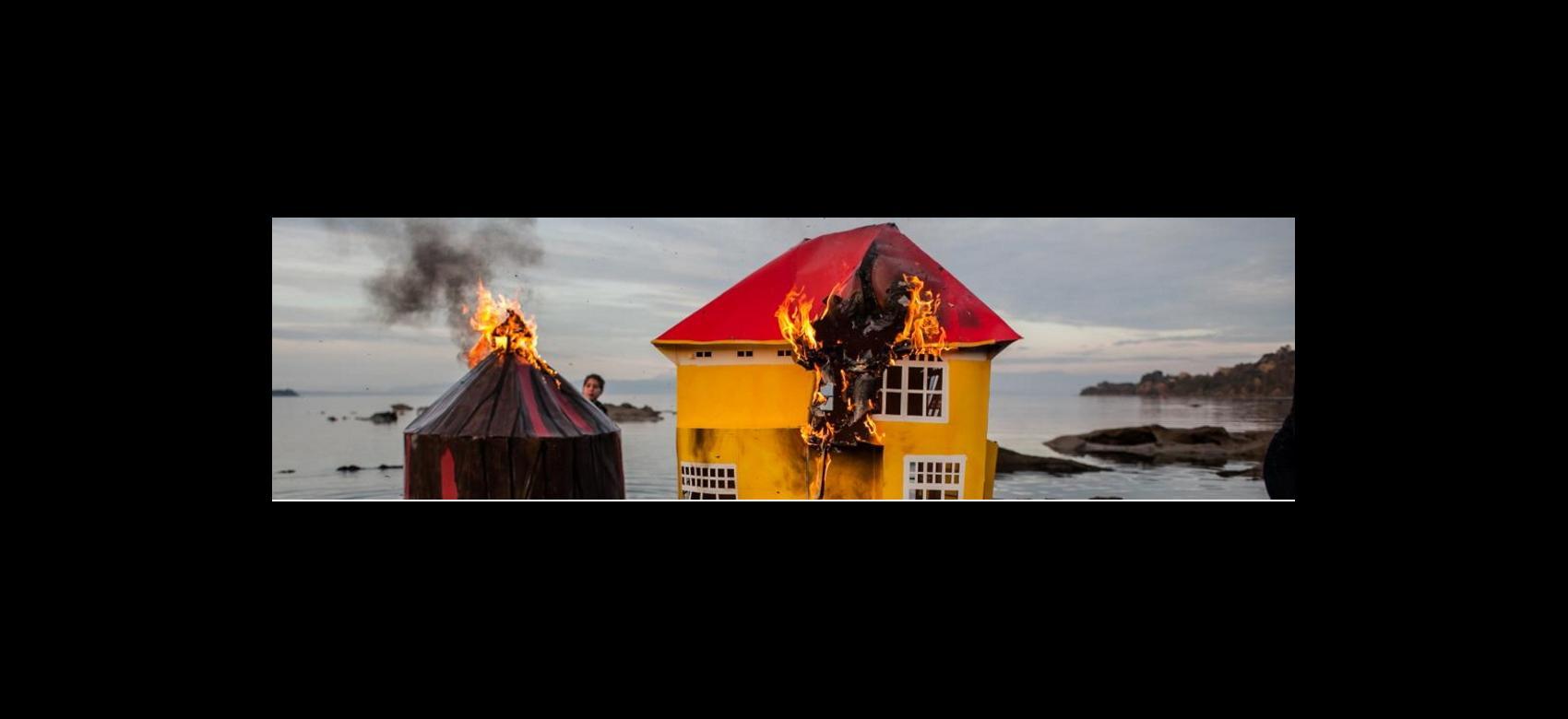 Casa con techo rojo prendiéndose fuego al fondo el mar