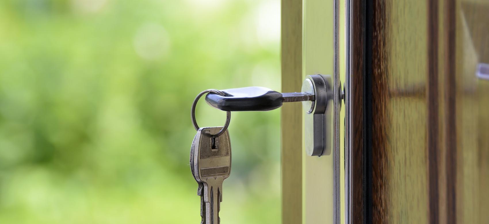 Llave en la cerradura de una puerta abriéndose