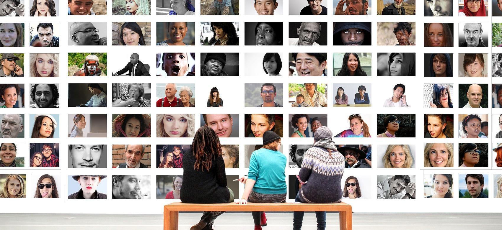 Jóvenes sentados mirando un panel con muchos rostros difernetes