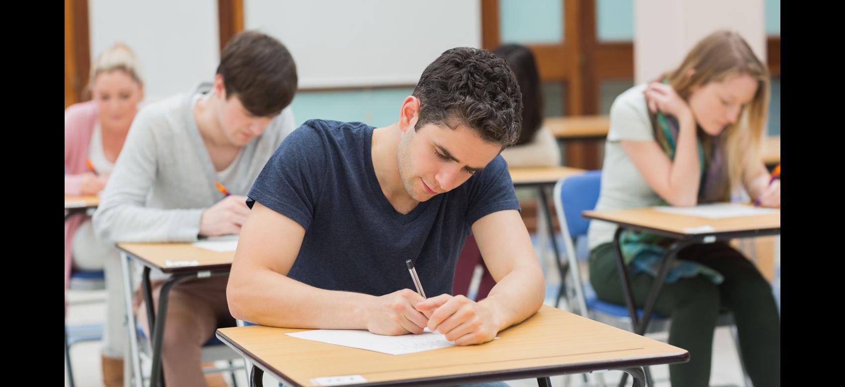 Chico joven inclinado sobre una mesa mientras escribe en una hoja de examen