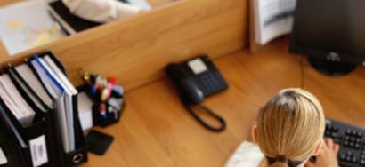 Mujer trabajando con un portátil, con teléfono a su izquierda
