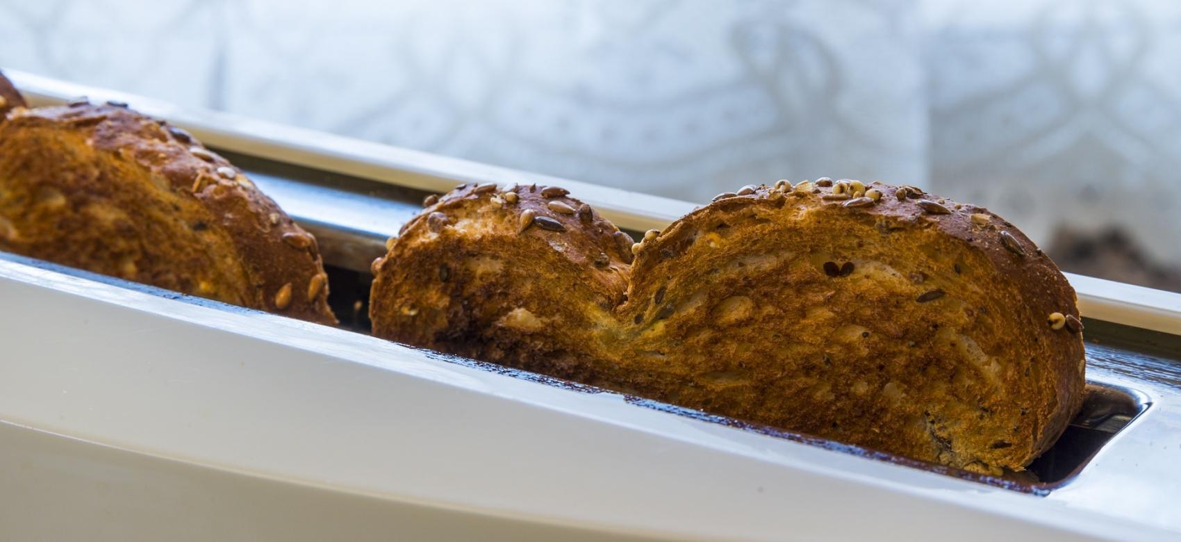 Tostador con rebanadas de pan de molde casi quemadas