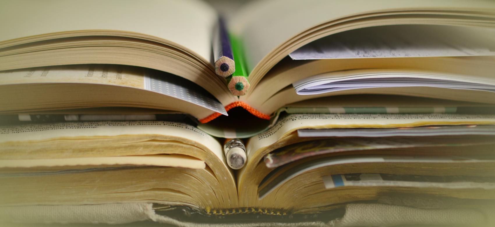 libro abierto con lapices de colores
