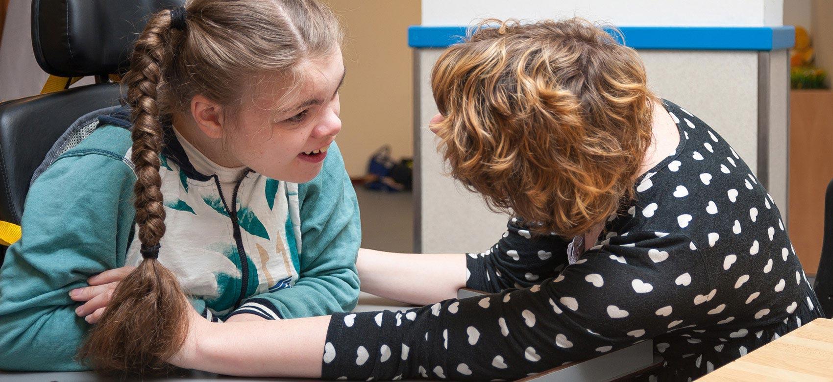 Trabajadora social atendiendo a una niña con discapacidad