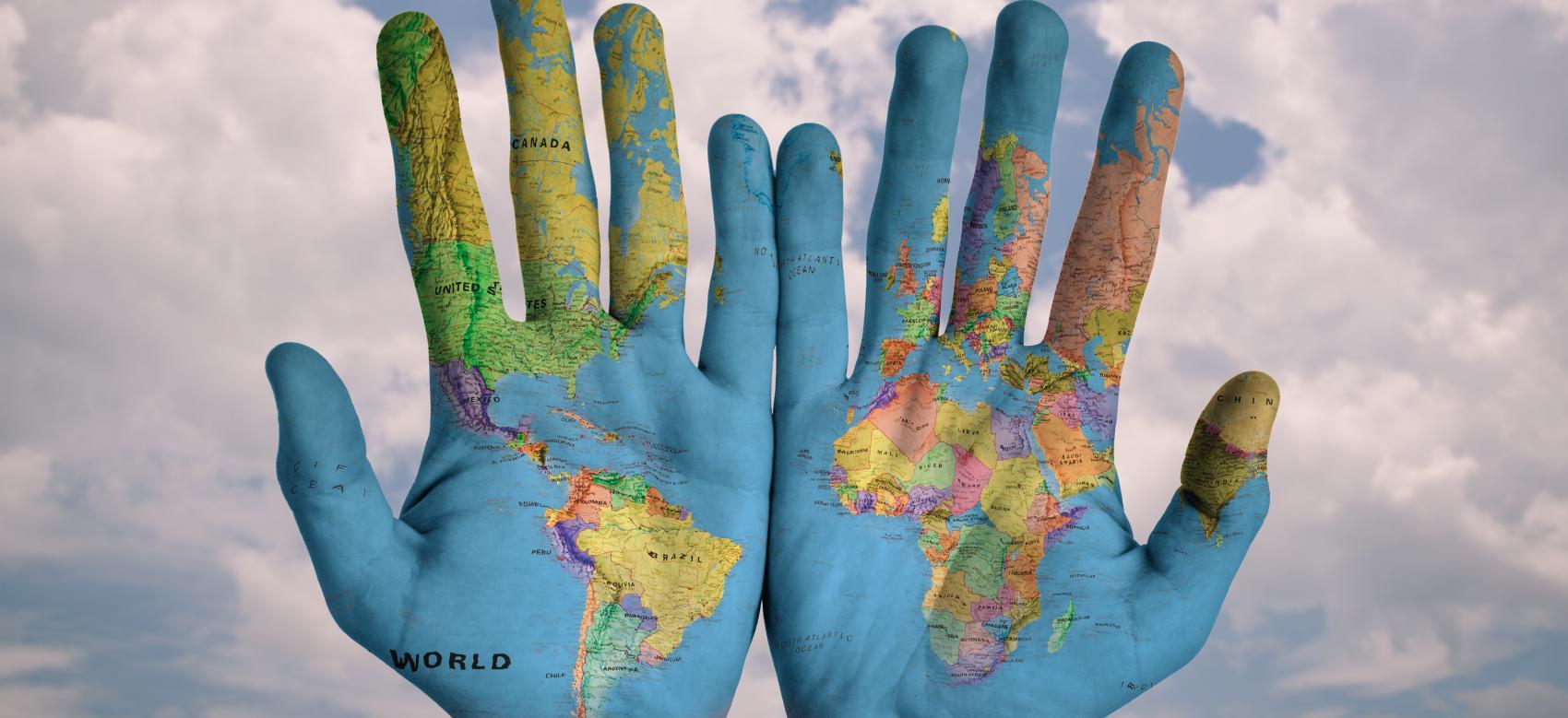 Manos con el mapa del mundo pintado