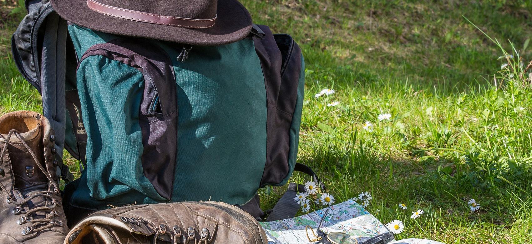 Unas botas de senderismo marrores, un plano, una brujula, una mochila de color azul y negra y encima de esta un sombrero de ala de color marrón oscuro
