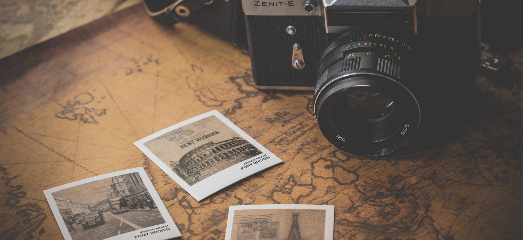 Se observa una imagen en tres planos. el primer plano es un mapa, el segundo plano son tres fotos polaroid de París, Roma y Londres. y el último plano es una cámara antigua fotográfica con su funda marron