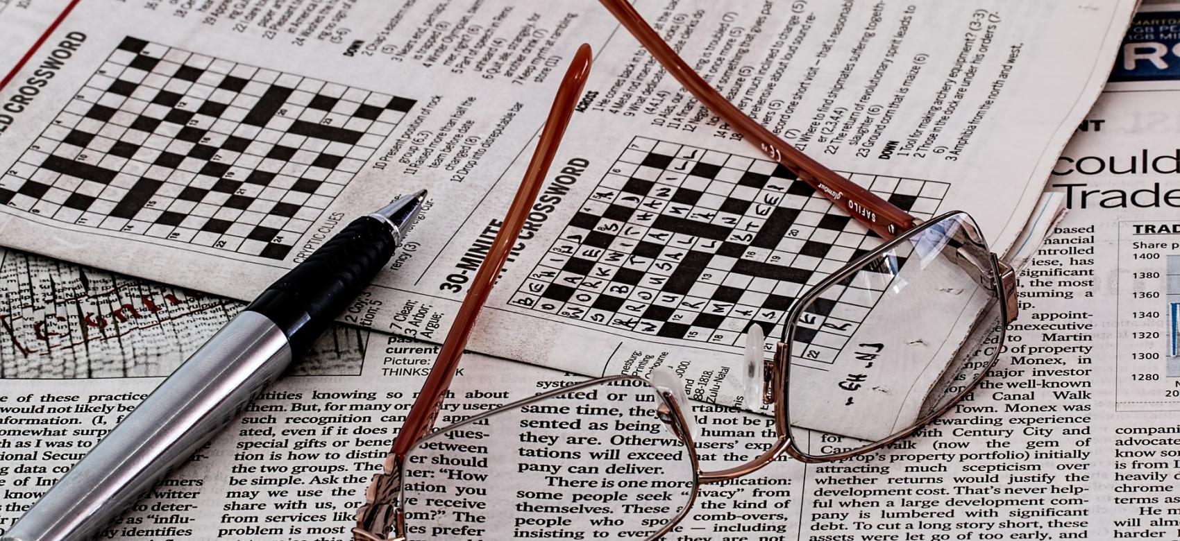 Periódico con bolígrafo y gafas encima