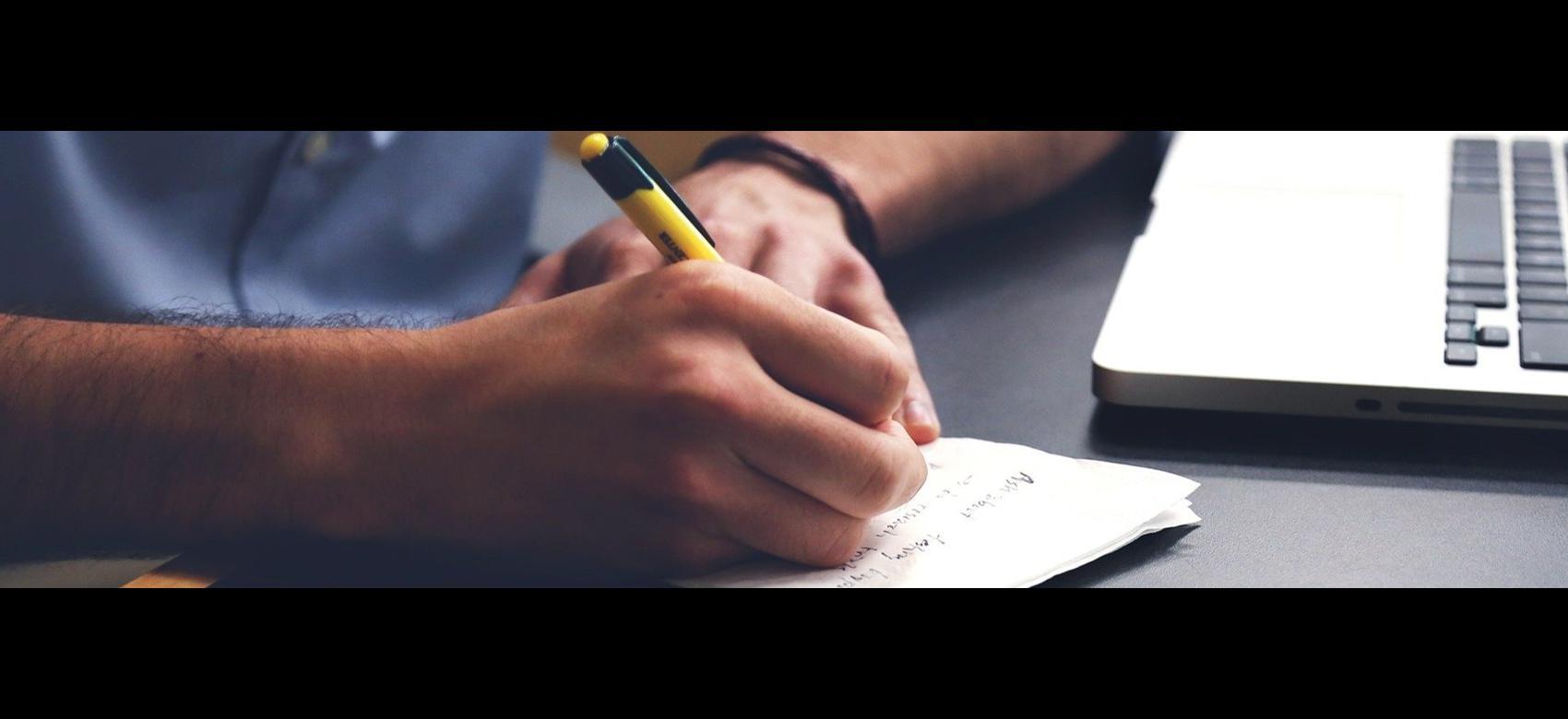 brazo de hombre con boligrafo escribiendo y parte de ordenador portátil leyenda trabajador autónomo y MVCL