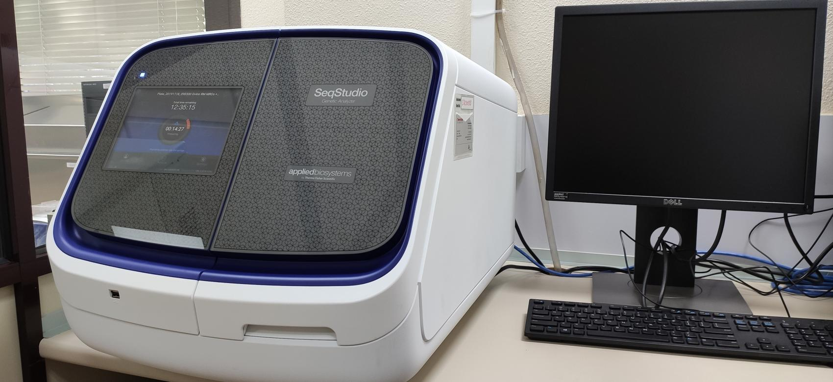 Secuenciador genético con pantalla de ordenador a su lado