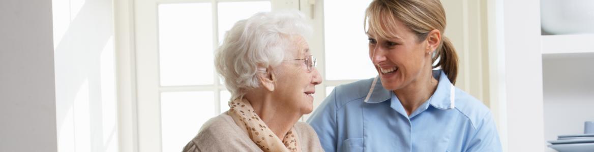 Mujer mayor caminando junto a cuidadora