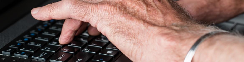 Primer plano de las manos de un hombre mayor sobre teclado de ordenador portátil