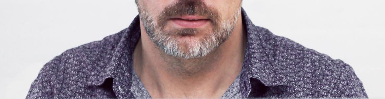 Primer plano de un hombre con barba canosa