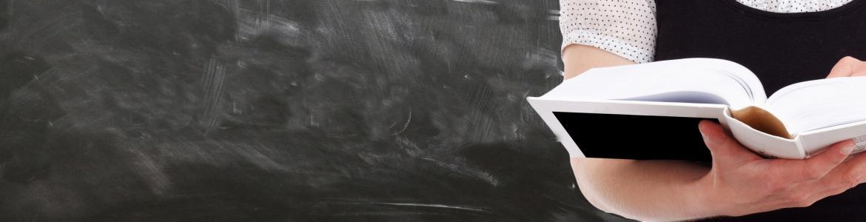 Estudiante sujetando libro con fondo de pizarra de aula