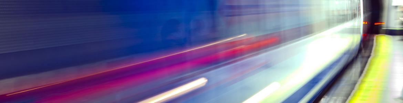 Imagen desenfocada de un vagón de metro en marcha cruzando un andén