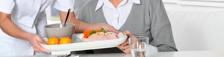 Mujer sirviendo comida a una mujer en una residencia de la tercera edad