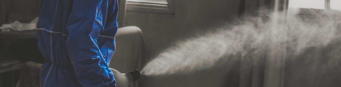 Persona con un traje de protección aplicando un desinfectante por pulverización