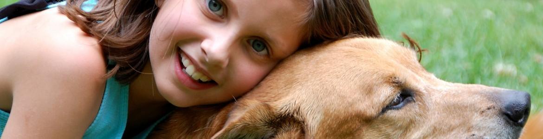 Niña abrazando a un perro en un parque