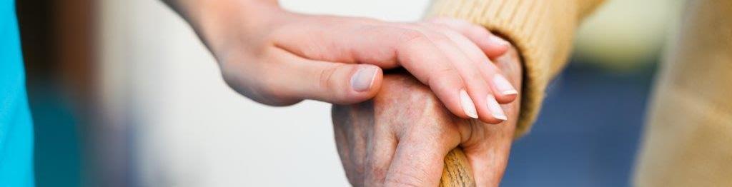 Mano de cuidadora sobre mano de persona mayor