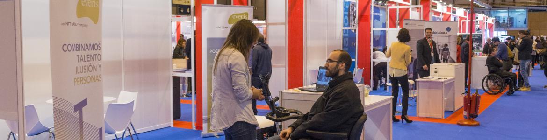 Un hombre en silla de ruedas habla con empleada de Everis en su stand de la X Feria de empleo para Personas con Discapacidad y III Foro de Activación del Empleo