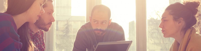 Personas sentadas alrededor de una mesa, en la que hay un portátil, durante una reunión de trabajo.