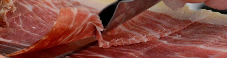 Imagen de una persona cortando una pata de jamón ibérico