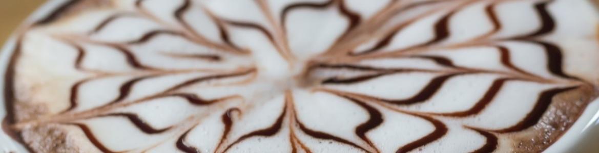 Imagen de una taza de café con espuma de leche decorada con un dibujo