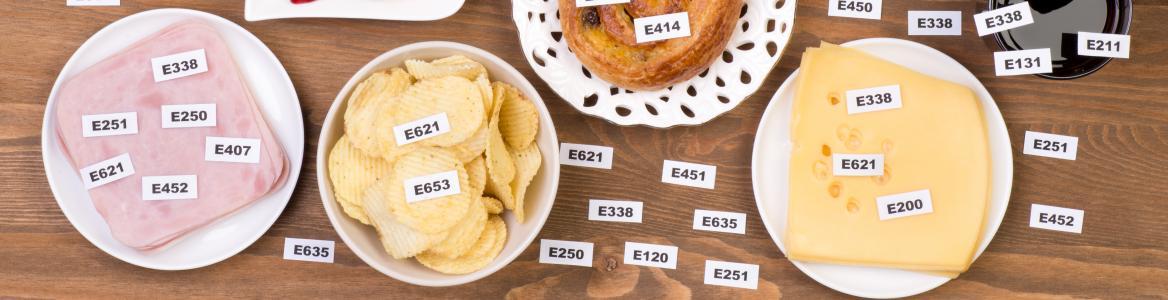 Varios alimentos que tienen identificados en un cartel los aditivos alimentarios que contienen