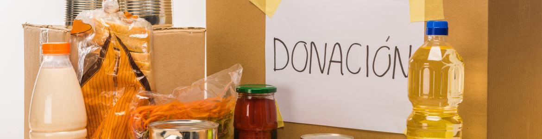 """caja con diversos alimentos y cartel """"donación"""""""