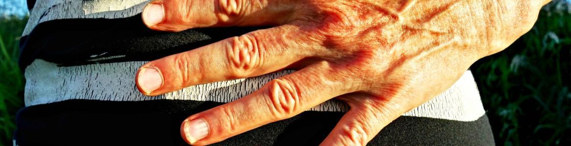 imagen del abdomen de una persona con una mano indicando dolor