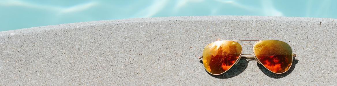 Gafas del sol al borde de la piscina