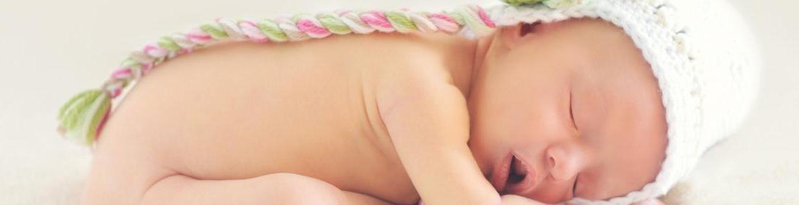 bebé recién nacido boca abajo con sombrero
