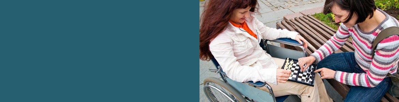 Mujer con discapacidad jugando al ajedrez con una amiga