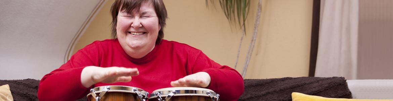 Imagen ilustrativa de una mujer con discapacidad tocando un instrumento de percusión
