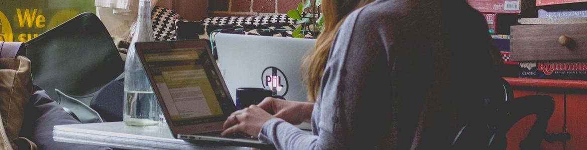Joven sentada en casa trabajando con el ordenador