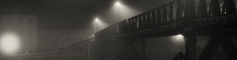 Imagen de un puente y casas al fondo, de noche, con bruma