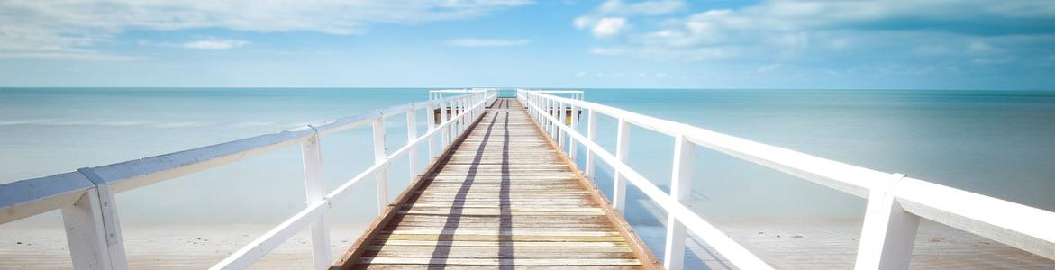Paseo de un embarcadero blanco al lado de un mar de un azul muy intenso.