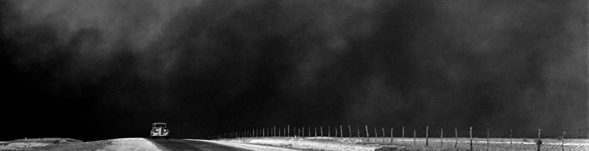 Imagen en blanco y negro de una carretera con un coche y el cielo lleno de polvo