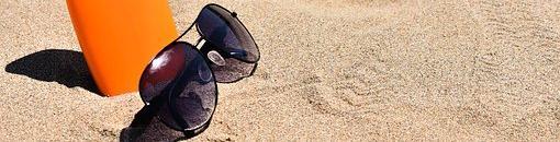 Gafas de sol y envase de crema protectora sobre arena de playa