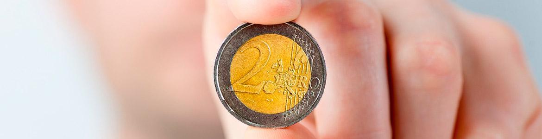 Imagen de moneda de dos euros entre los dedos.