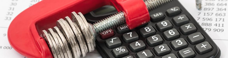 Imagen de monedas sujetas con un tornillo de presión sobre calculadora