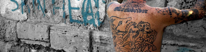 Imagen de una persona de espaldas con un tatuaje, apoyo en una pared con un grafiti