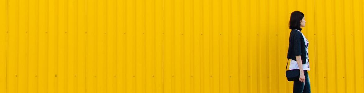 Chica caminando con una pared amarilla de fondo